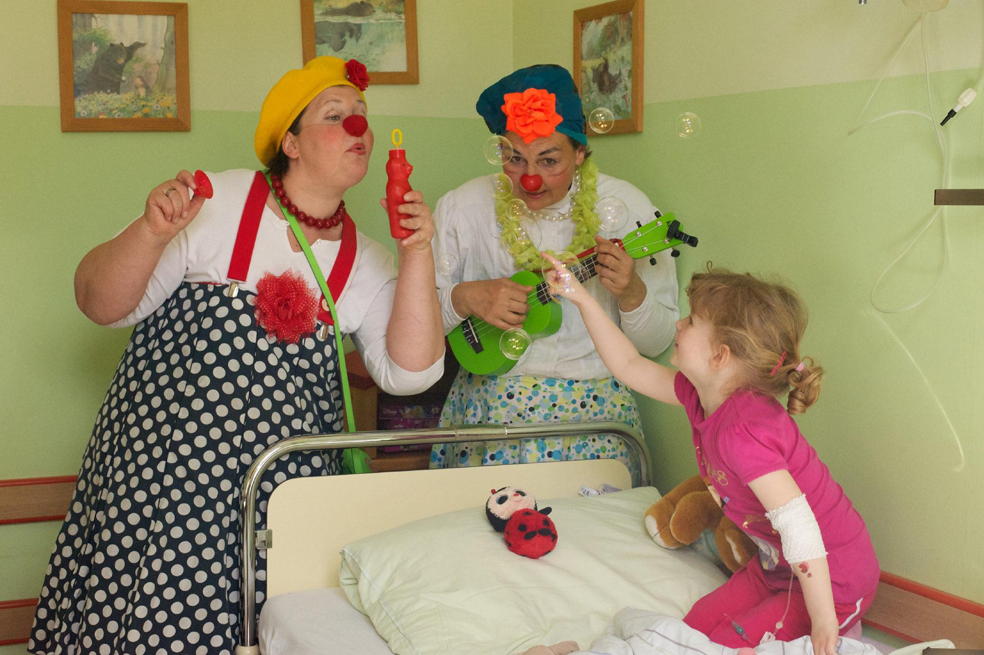 Clowns und Kind am Klinikbett